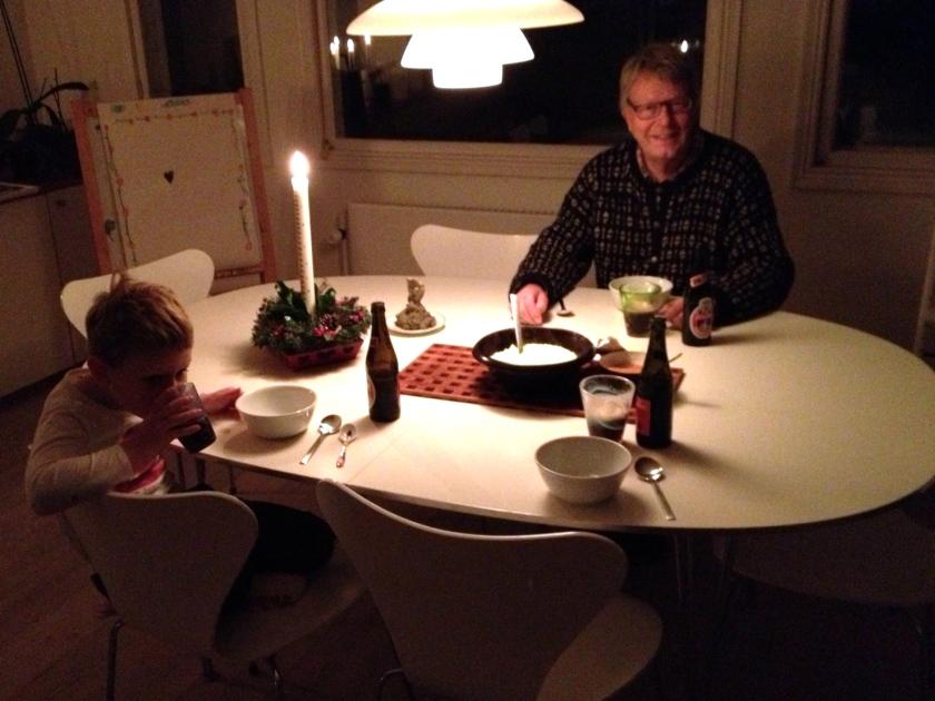 Familien samlet om den varme grød. Bemærk Peters kunstneriske juledekoration i baggrunden. Foto: Lotte Lund