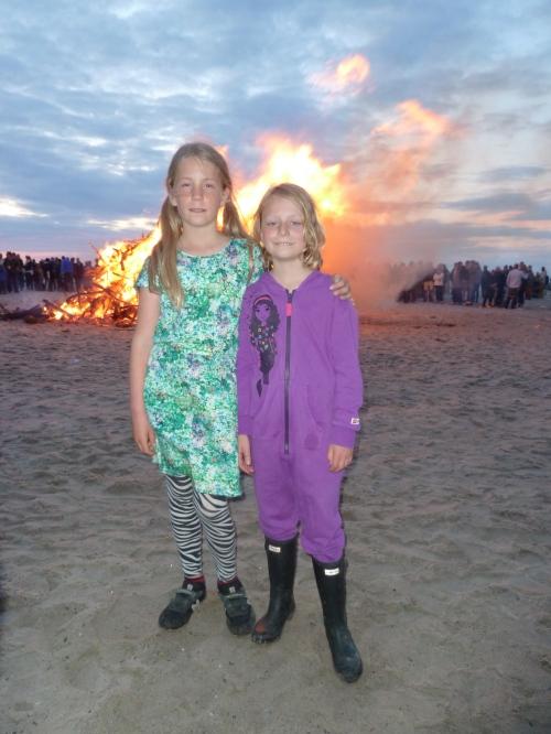 Freja og Thea varmer sig ved bålet. Foto: Lotte Lund.